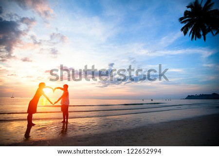 Young couple holding hands heart-shaped on the sea beach at sunset - stock photo