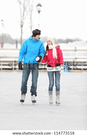 Young couple holding hands iceskating outdoors on a frozen lake or open-air rink against a snowy winter landscape - stock photo