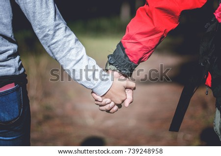 Young couple holding hands in forest, traveling concept