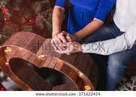 Young couple holding hands in front of a Christmas tree. - stock photo