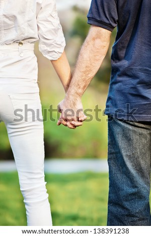 Young couple holding hands in park