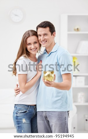 Young couple holding hands in the piggy bank - stock photo
