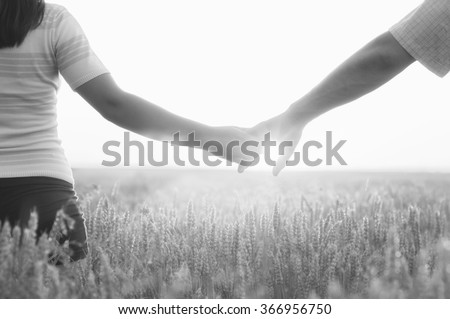 Young couple holding hands in the wheat field on sunny summer day. - stock photo