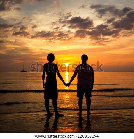 Young couple holding hands on the sea beach at sunset - stock photo