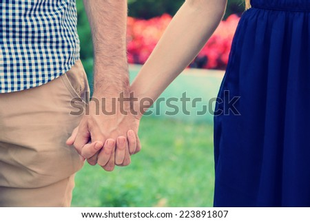 Young couple holding hands, outdoors