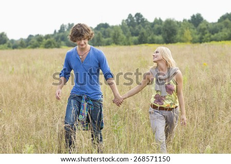 Young couple holding hands while walking through field - stock photo