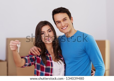Young couple holding keys in hand to their new home - stock photo