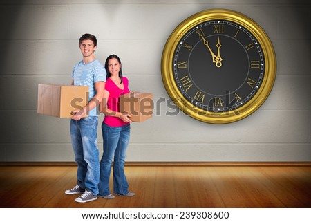 Young couple holding moving boxes against room with wooden floor - stock photo