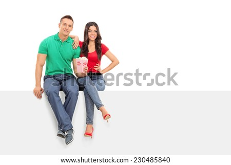 Young couple holding popcorn seated on a panel isolated on white background - stock photo
