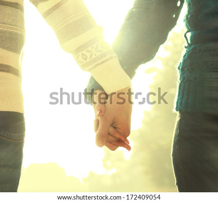 young couple holds hands on the nature - stock photo