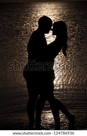 Young couple hug silhouette on a sea beach against sunset background