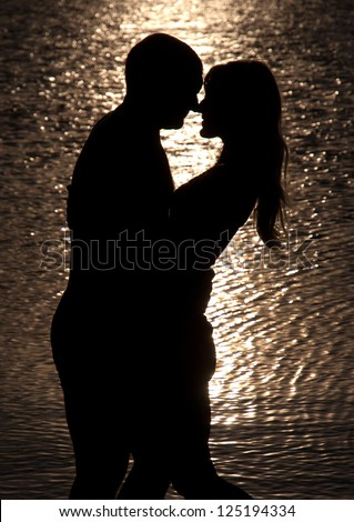 Young couple hug silhouette on a sea beach against sunset background - stock photo