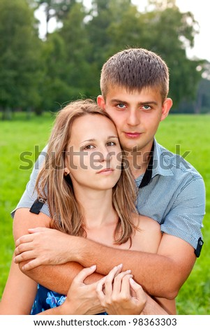 Young couple hugging against a background of green nature