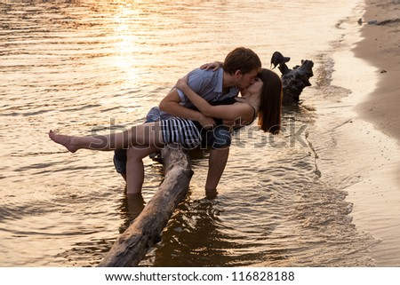 Young couple hugging and kissing at riverside at sunset. Young Couple Hugging Kissing Riverside Sunset Stock Photo