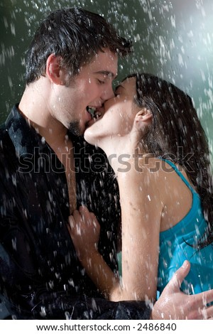 Young couple hugging and kissing under a rain, in passion