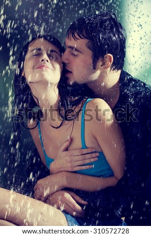Young couple hugging and kissing under a rain, in passion - stock photo