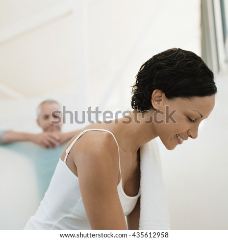 Young couple hugging and smiling at each other at home in the bathroom