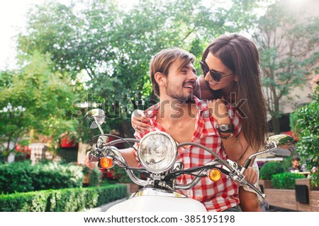 Young couple hugging on a retro scooter outdoors on a summer day - stock photo