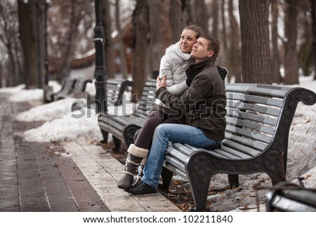 Young couple hugging on bench in park - stock photo