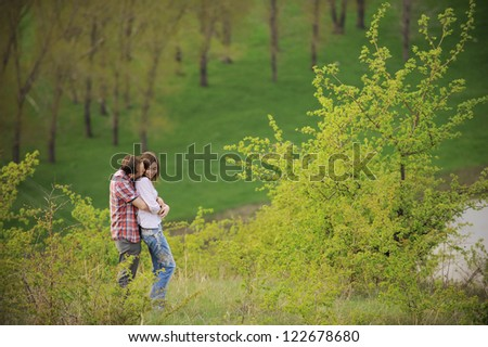 young couple hugging on hill