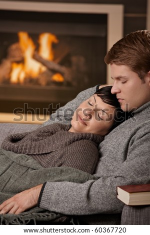 Young couple hugging on sofa in front of fireplace at home, woman sleeping.
