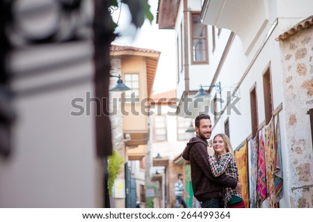 Young couple hugging outdoors in old European town. Romantic happy woman and man enjoying life and romance outside. - stock photo