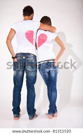 Young couple hugging.Their shirts making single heart - stock photo