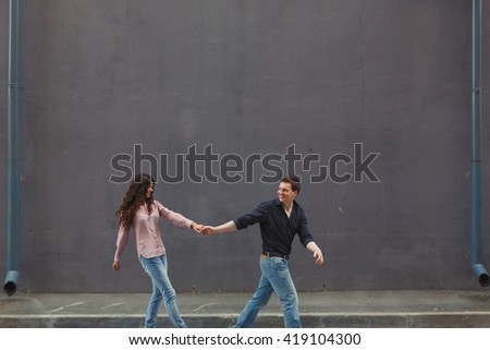 Young couple hugging while sitting on staircase. Industrial background - stock photo