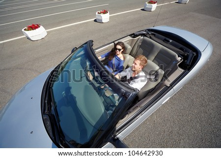 Young couple  in a dark sunglasses rides in a cabriolet - stock photo