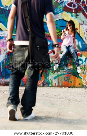 Young couple in a graffiti background - stock photo