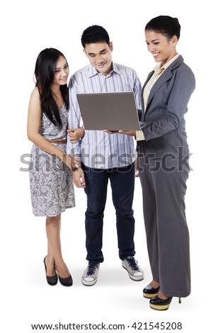 Young couple in a meeting with female consultant while standing on white background - stock photo