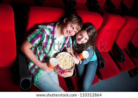 young couple in a movie theater, hugging and happy to have a good time together - stock photo