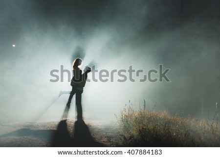 Young couple in a park at night or in the countryside. Backlight and smoke or fog. In the hands of orange or red balloons