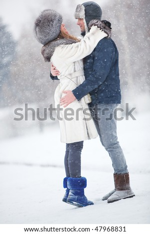 Young couple in a park. Winter season.