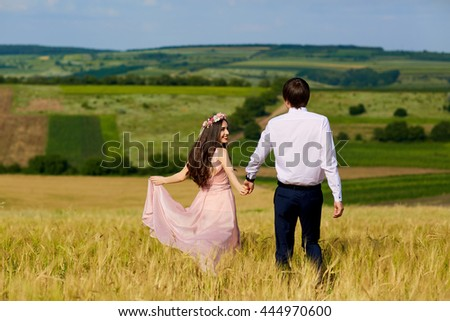 Young couple in a romantic place. Couple in love outdoors in a wheat field embracing, looking forward.