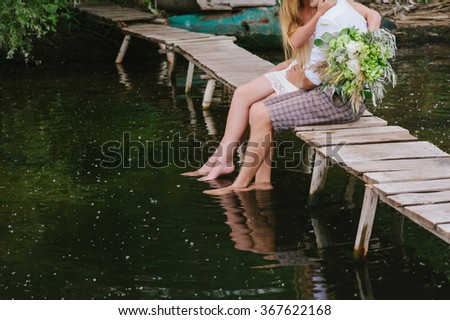 Young couple in a wreath with a bouquet on a wooden bridge laughing, lifestyle, love, romance, relationships