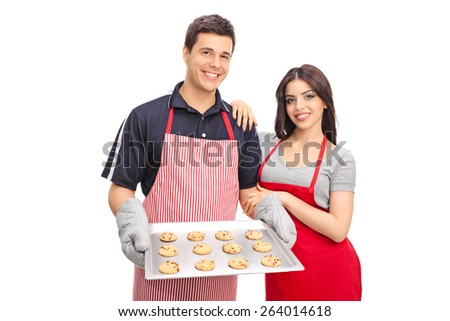Young couple in aprons holding a pan with chocolate chip cookies and looking at the camera isolated on white background  - stock photo