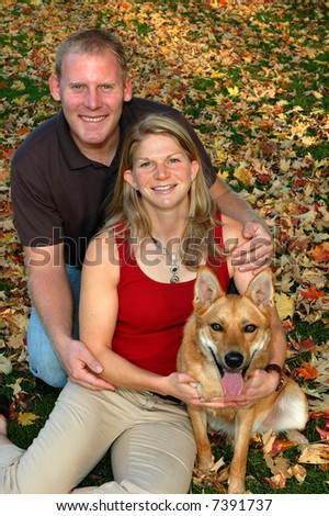 young couple in autumn leaves with their dog