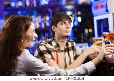 Young couple in bar having drinks and talking - stock photo