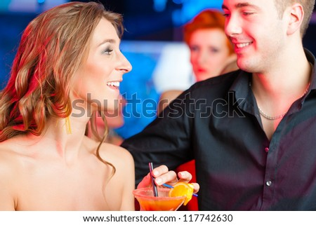 young couple in bar or club drinking cocktails, it might be the first date - stock photo