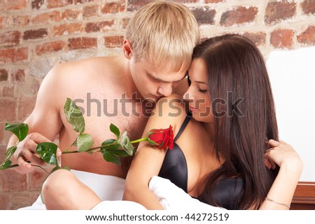 Young couple in bed with a rose