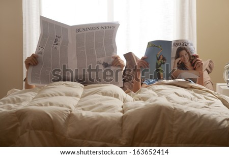 Young couple in bedroom reading newspaper and magazine - stock photo