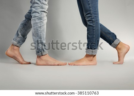 Young couple in blue jeans standing on grey background