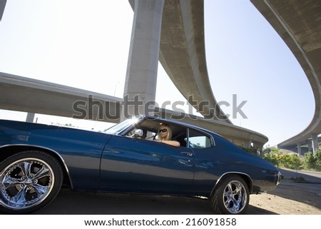 Young couple in car beneath overpass, low angle view (lens flare)