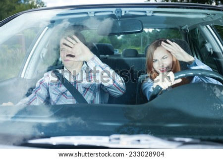 Young couple in car blinded by high beam lights - stock photo