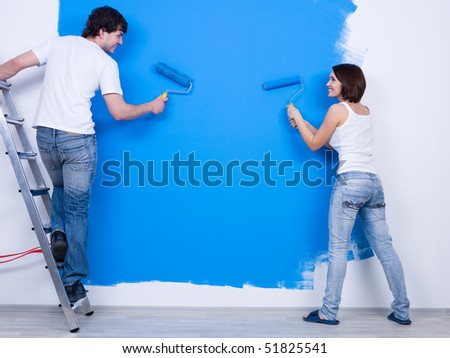 Young couple in casuals ?oloring the wall in blue - rear view