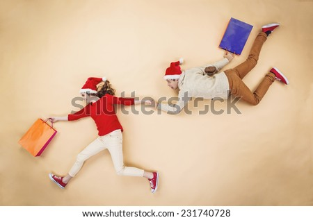 Young couple in Christmas hats having fun running with shopping bags against the beige background - stock photo