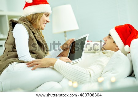 Young couple in Christmas hats using laptop