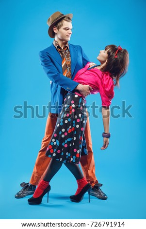 Young couple in colorful old-fashion clothes in pinup style dancing