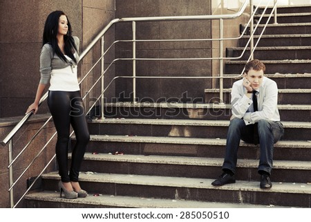 Young couple in conflict on the steps - stock photo